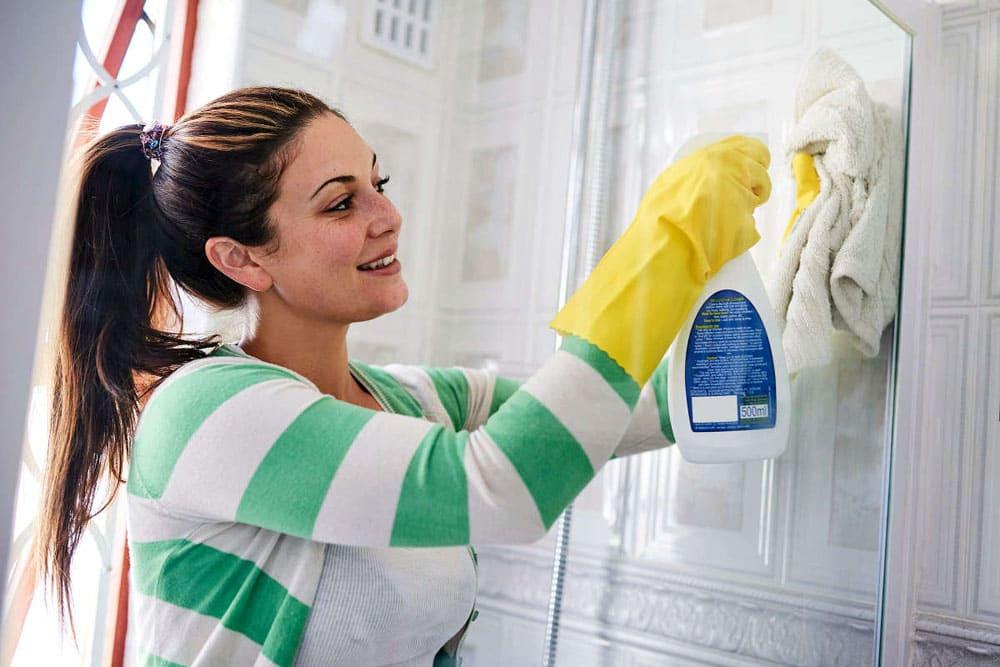 Девушка чистит душевую кабину